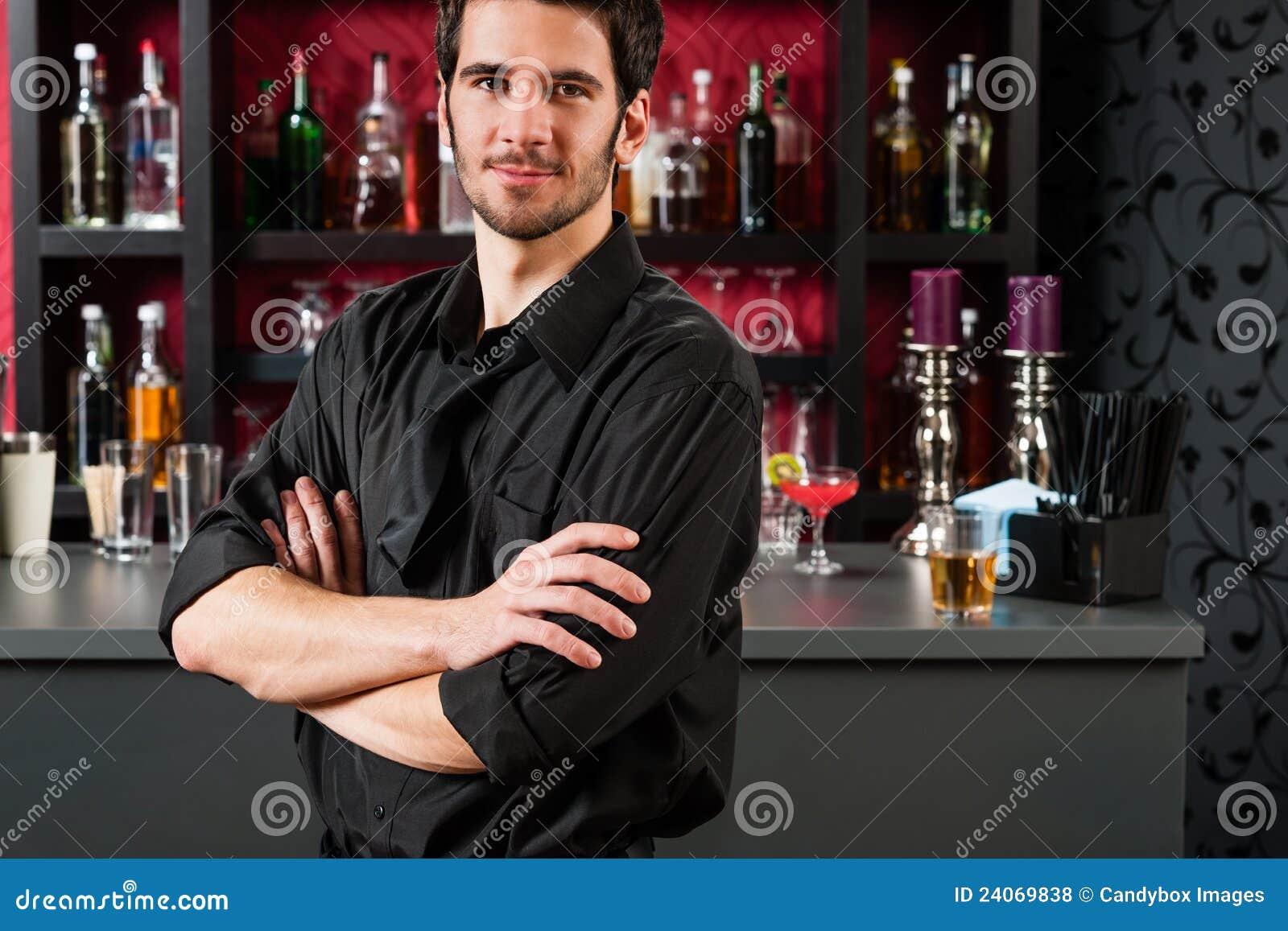 Barman in zwarte status bij cocktailstaaf