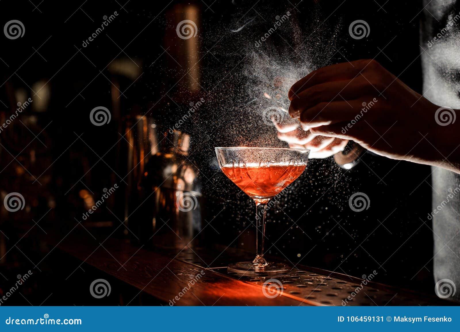 Barmans räcker att strila fruktsaften in i coctailexponeringsglaset