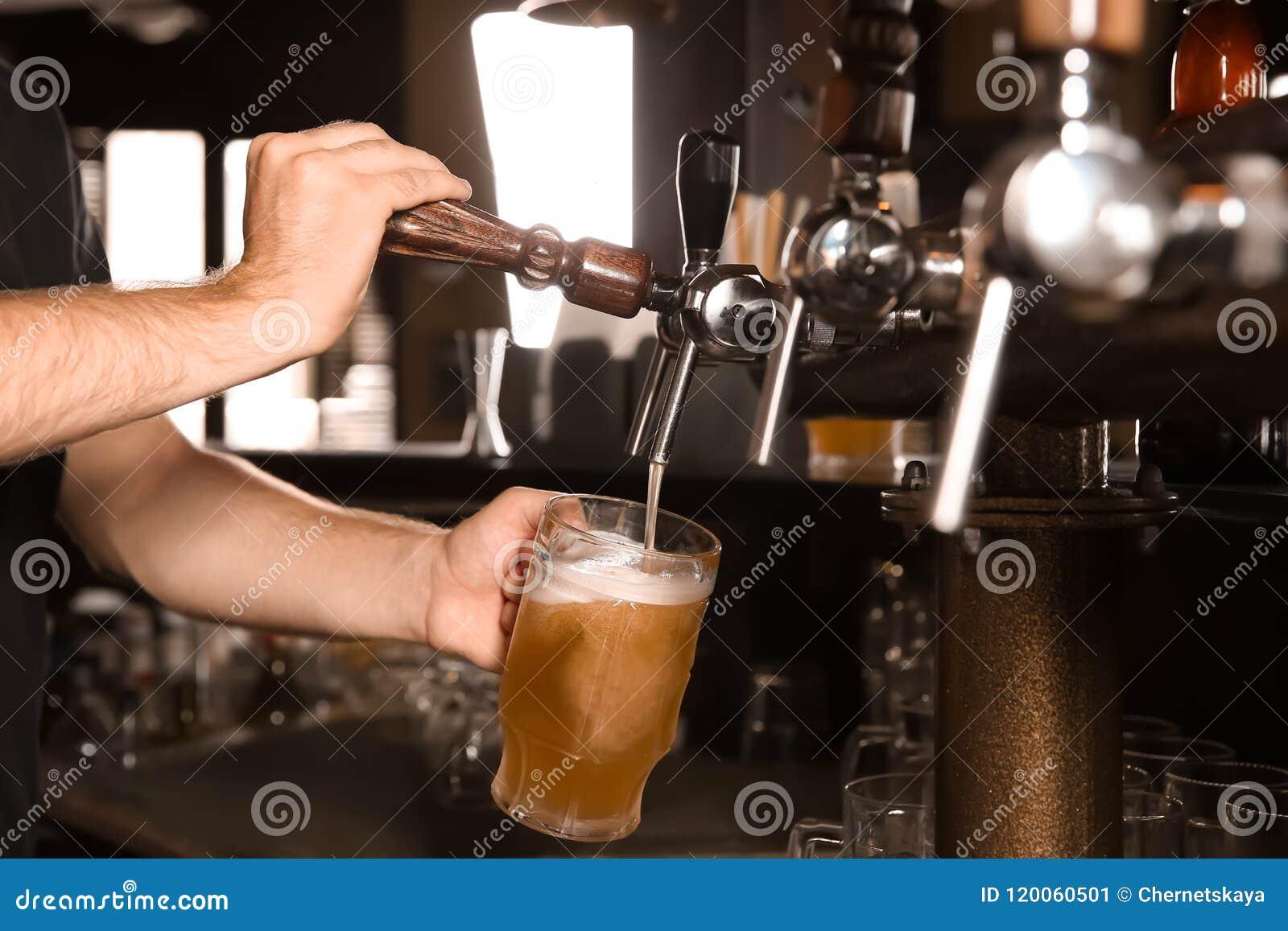 Barmanu dolewania piwo od klepnięcia w szkło w barze