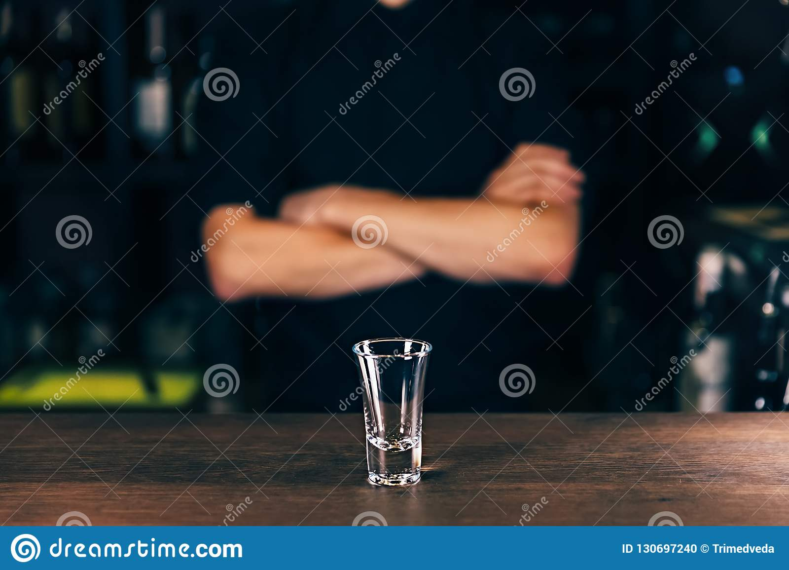 Barmany wręczają z butelki dolewania napojem w szkło Barman nalewa silnego alkoholicznego napój w małego szkło na barze