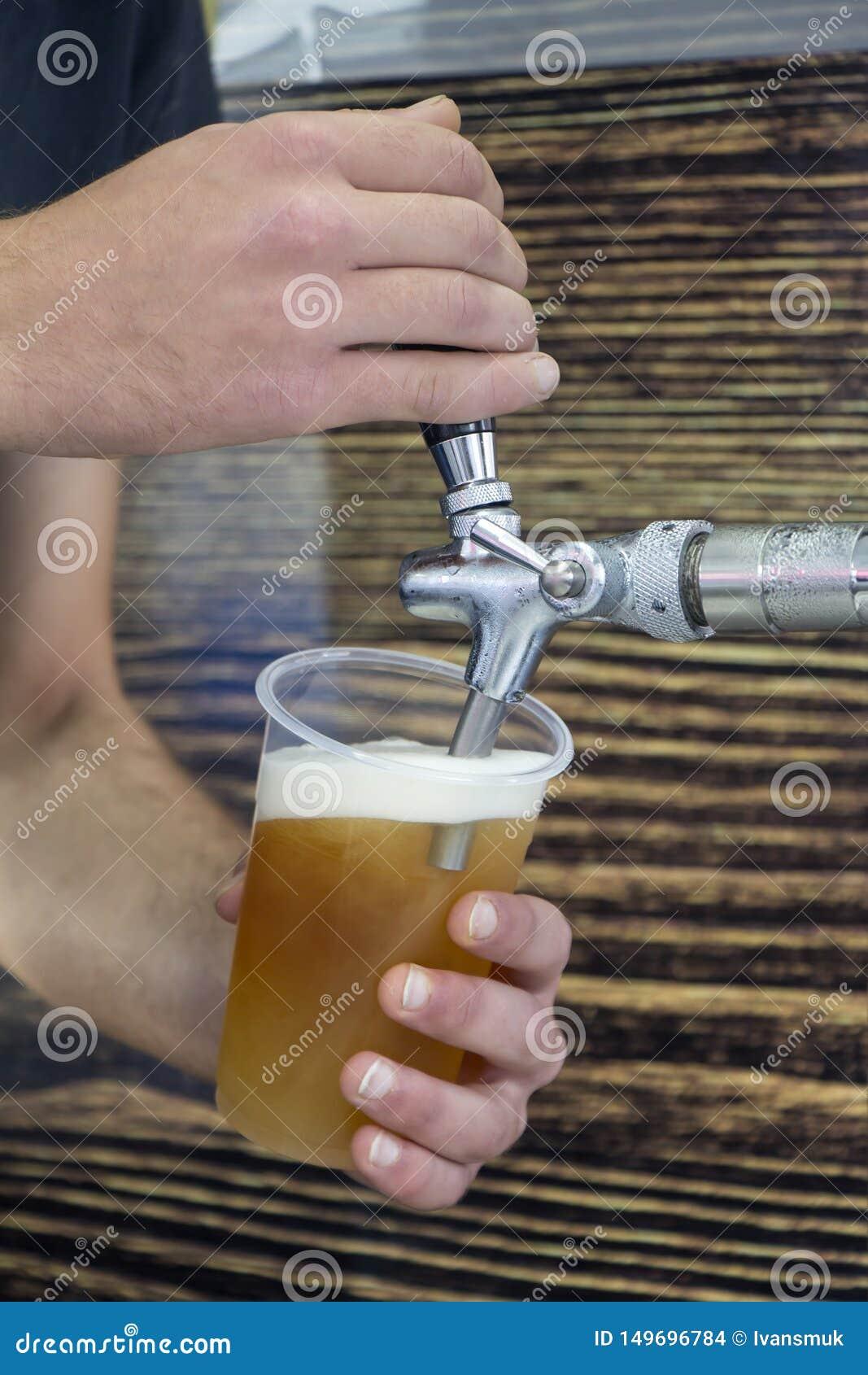 Barmany wypełnia plastikowego szkło z piwem