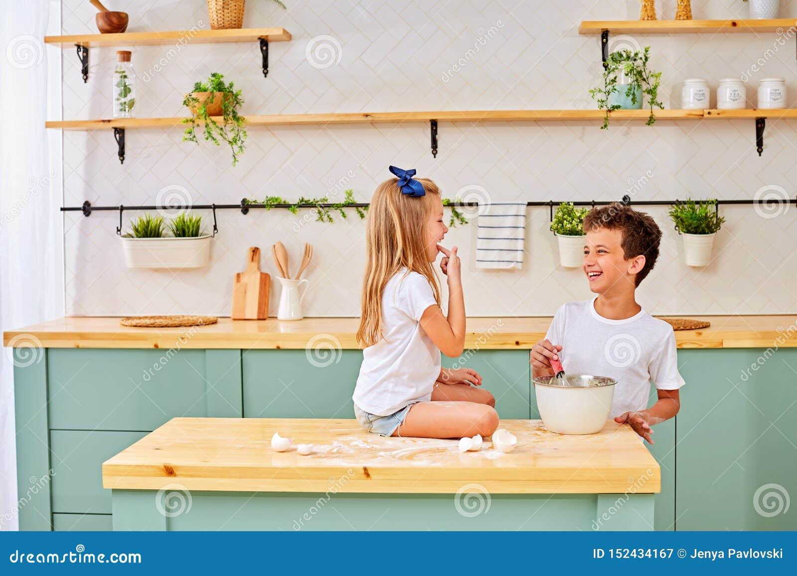 Barn en pojke och en flicka knådar en deg av mjöl och ägg och förbereder läckert