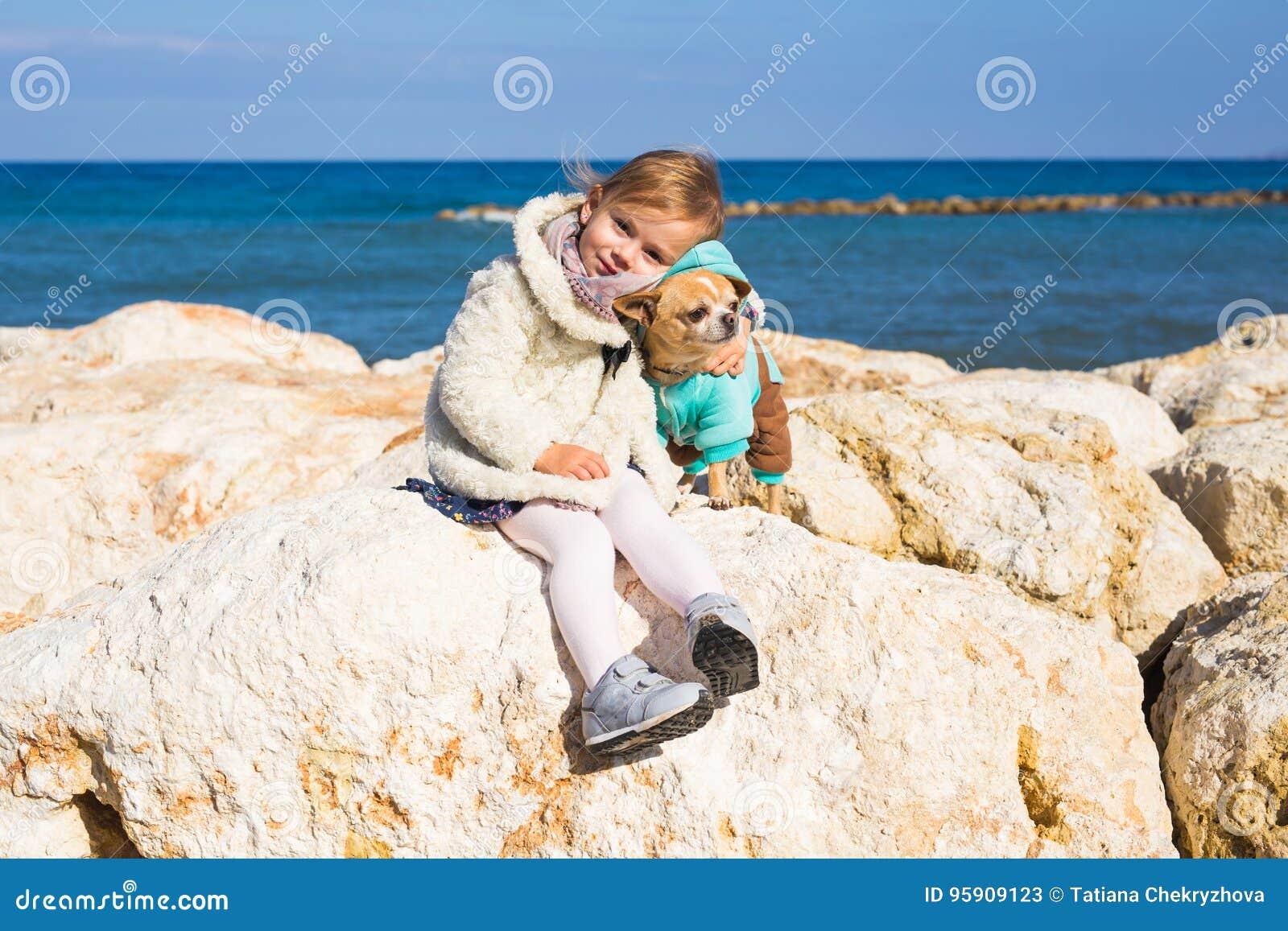 Barn-, husdjur-, sommar- och semesterbegrepp - liten flicka med chihuahuahunden på kusten