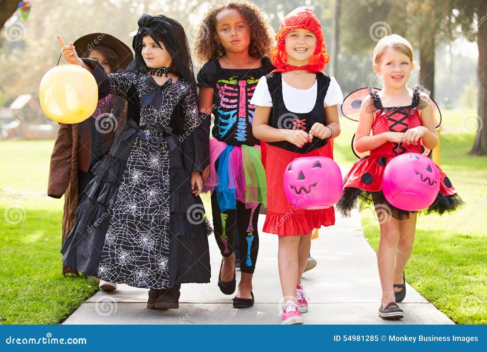 Barn, i trick eller behandling för utsmyckad dräktklänning gående