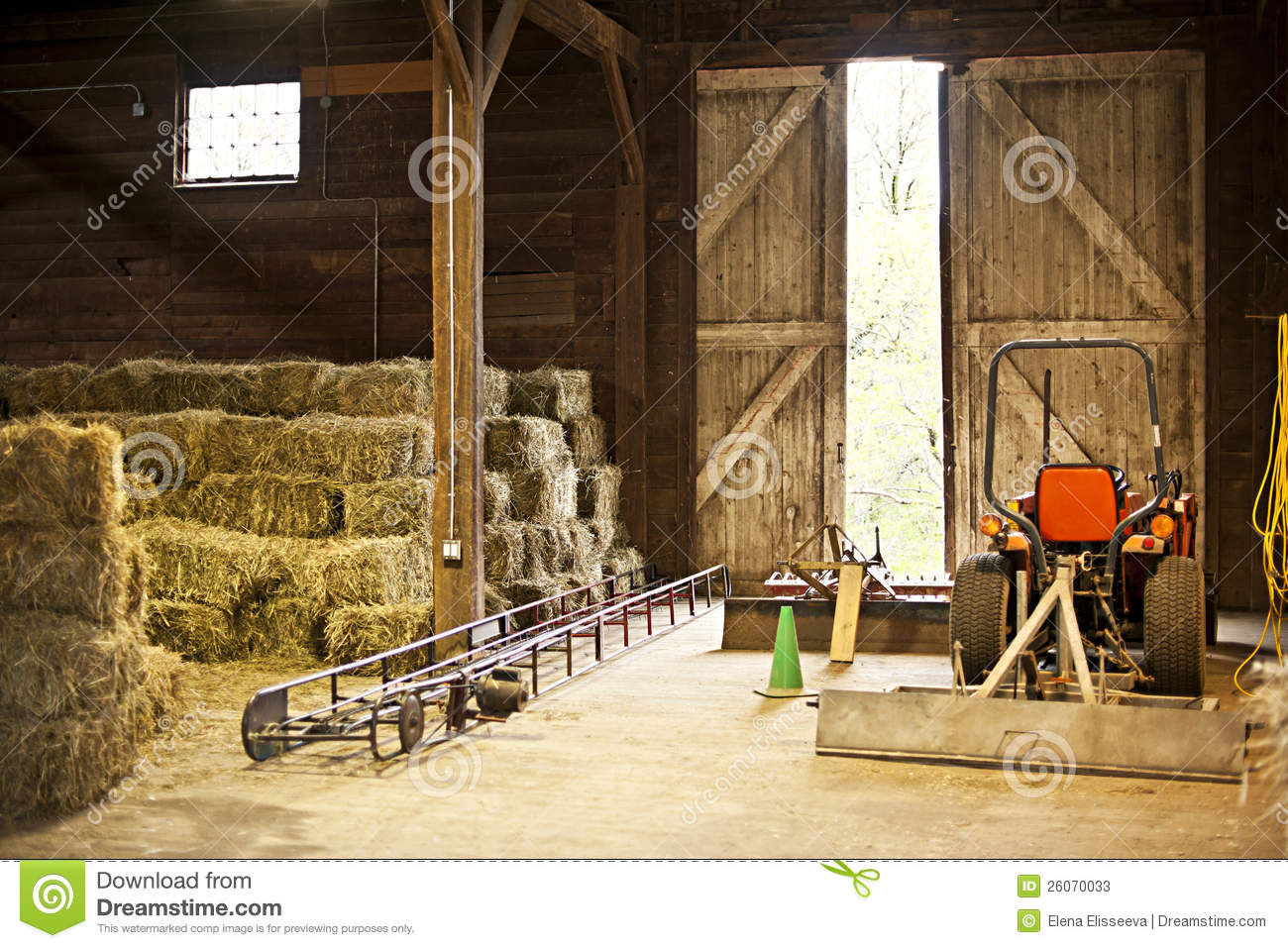 Barn Interior With Hay Bales And Farm Equipment Stock
