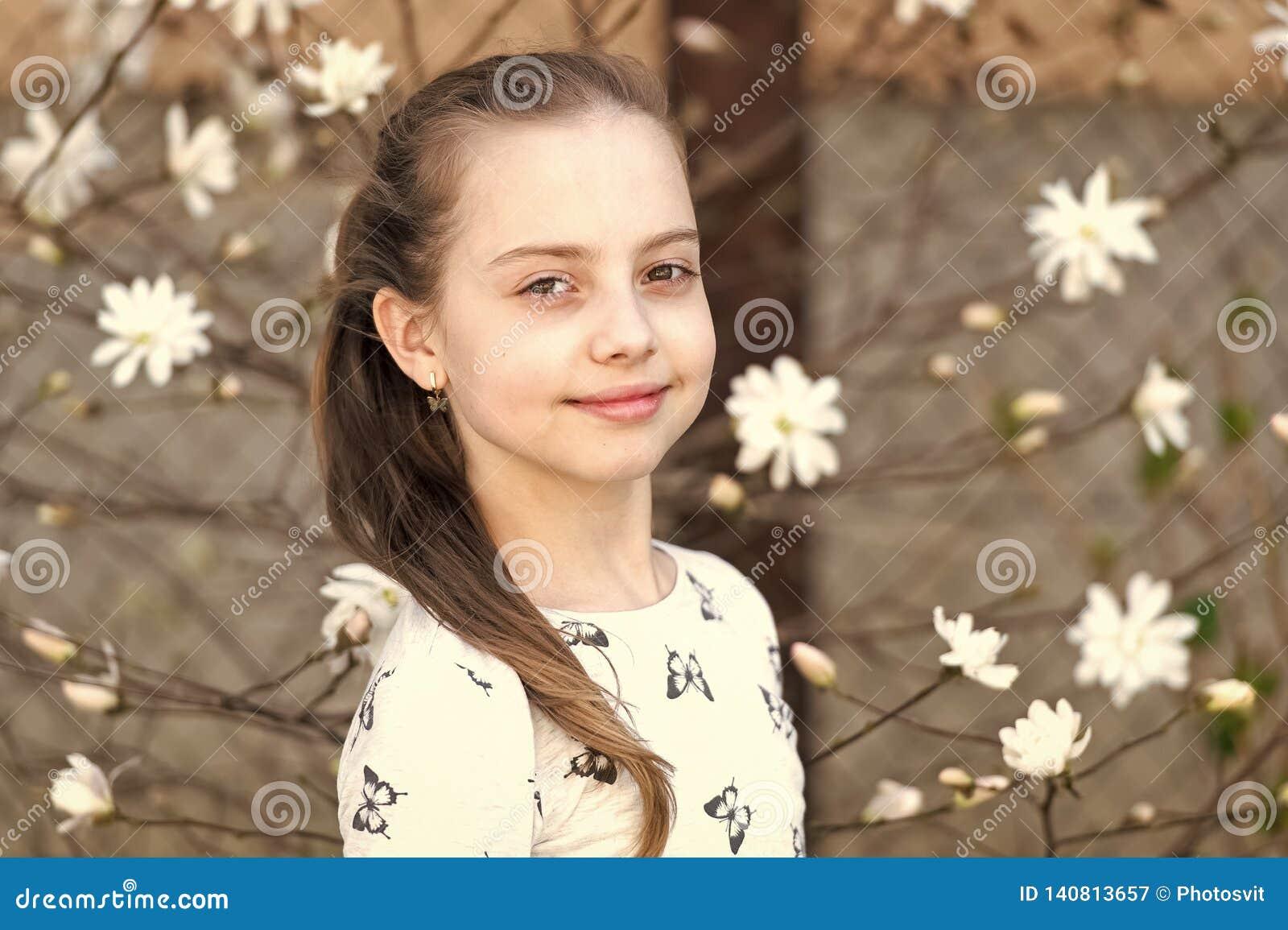 Barn med att blomstra utomhus- blommor Liten flicka på den blom- blomningen i vår Skönhetunge med ny blick och långt hår