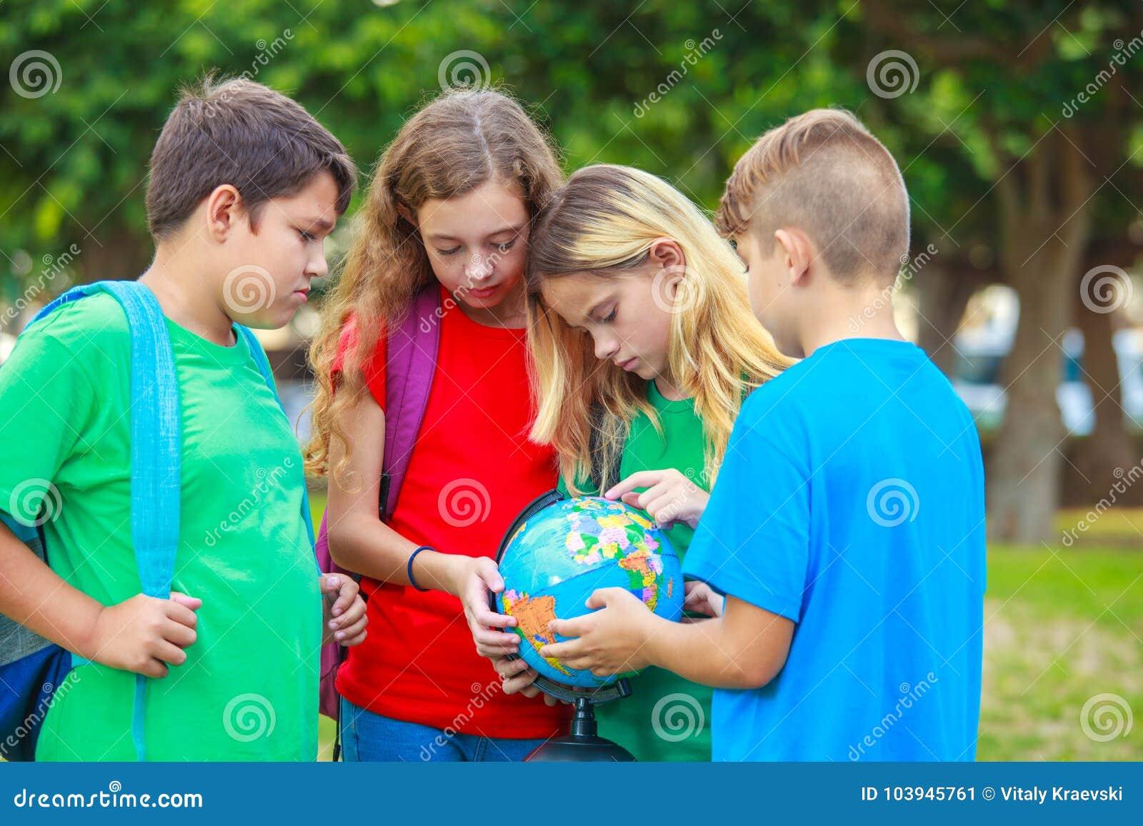 Barn med ett jordklot lär geografi