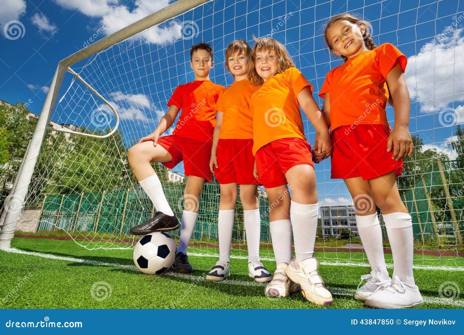 Barn med fotboll i rad nära träverk