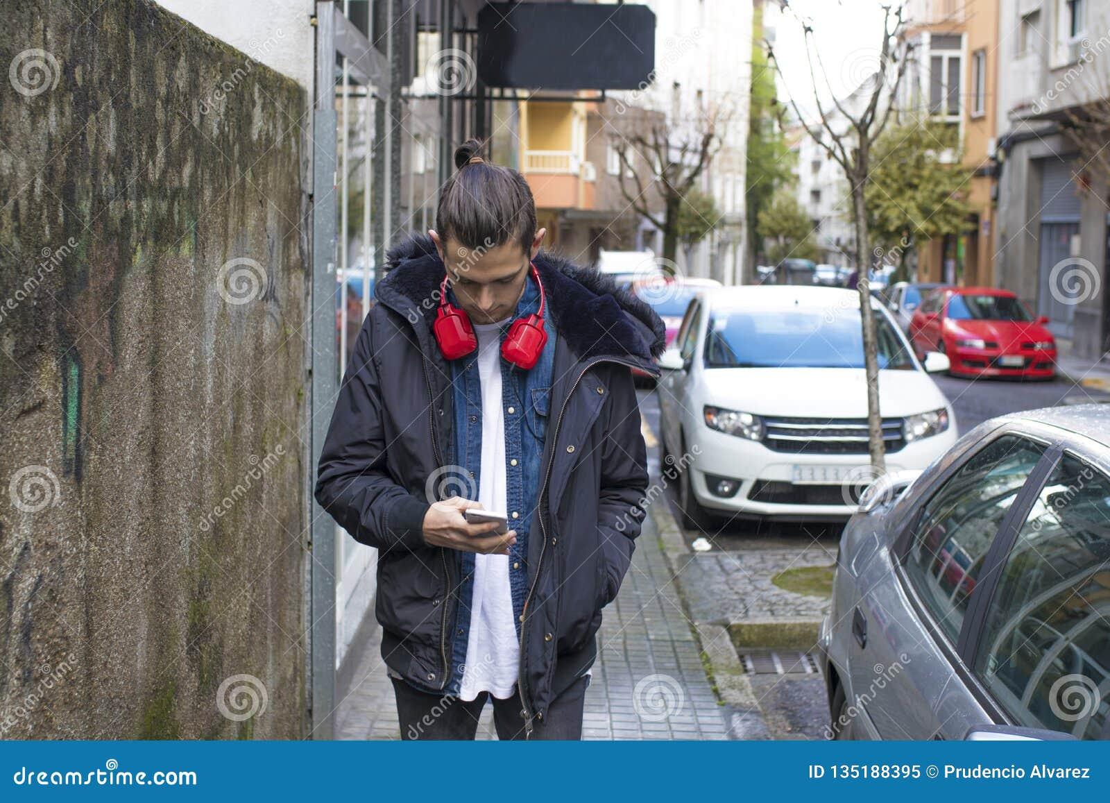 Barn med mobiltelefonen på gatan