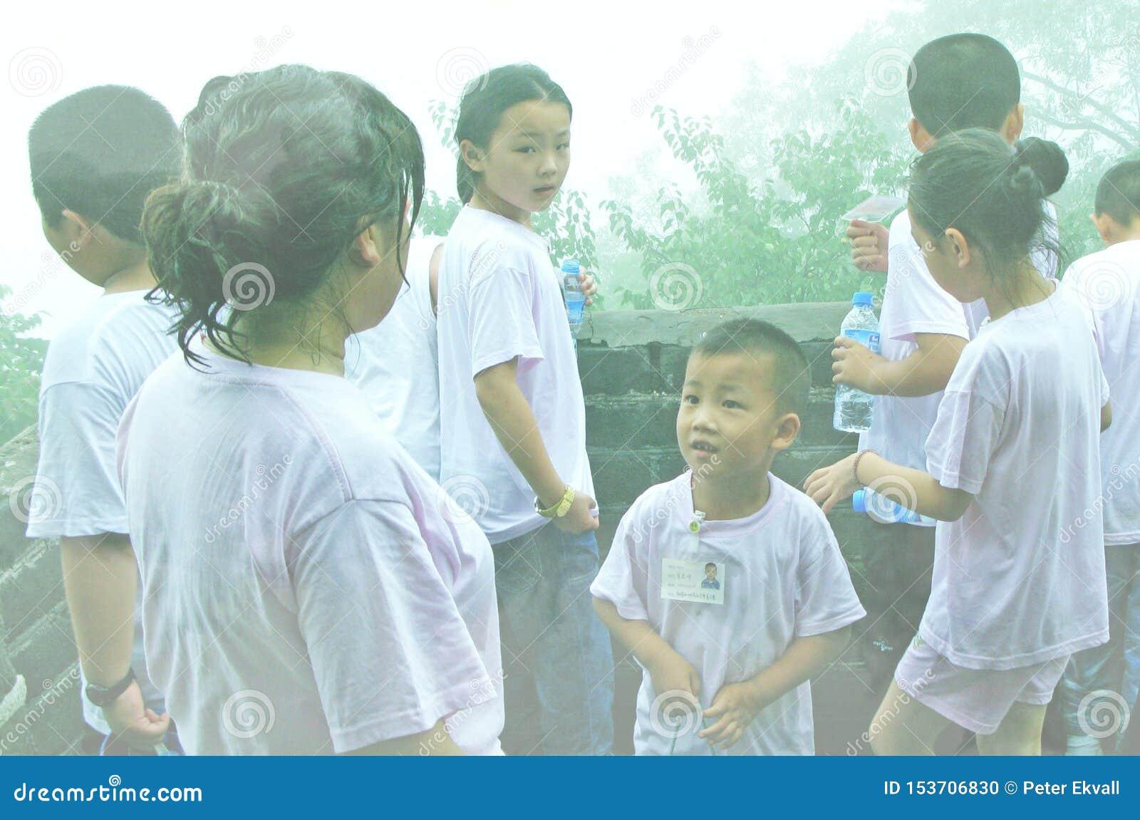 Barn och moder på den kinesiska väggen som är bifogad i dimma