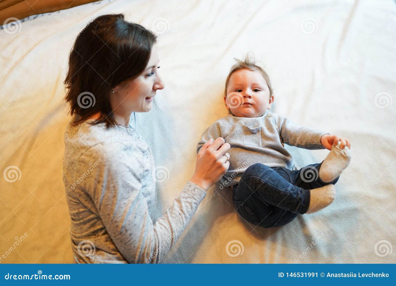 Barn och moder på säng Mamman och behandla som ett barn pojken som spelar i soligt sovrum F?r?lder och liten unge som hemma koppl