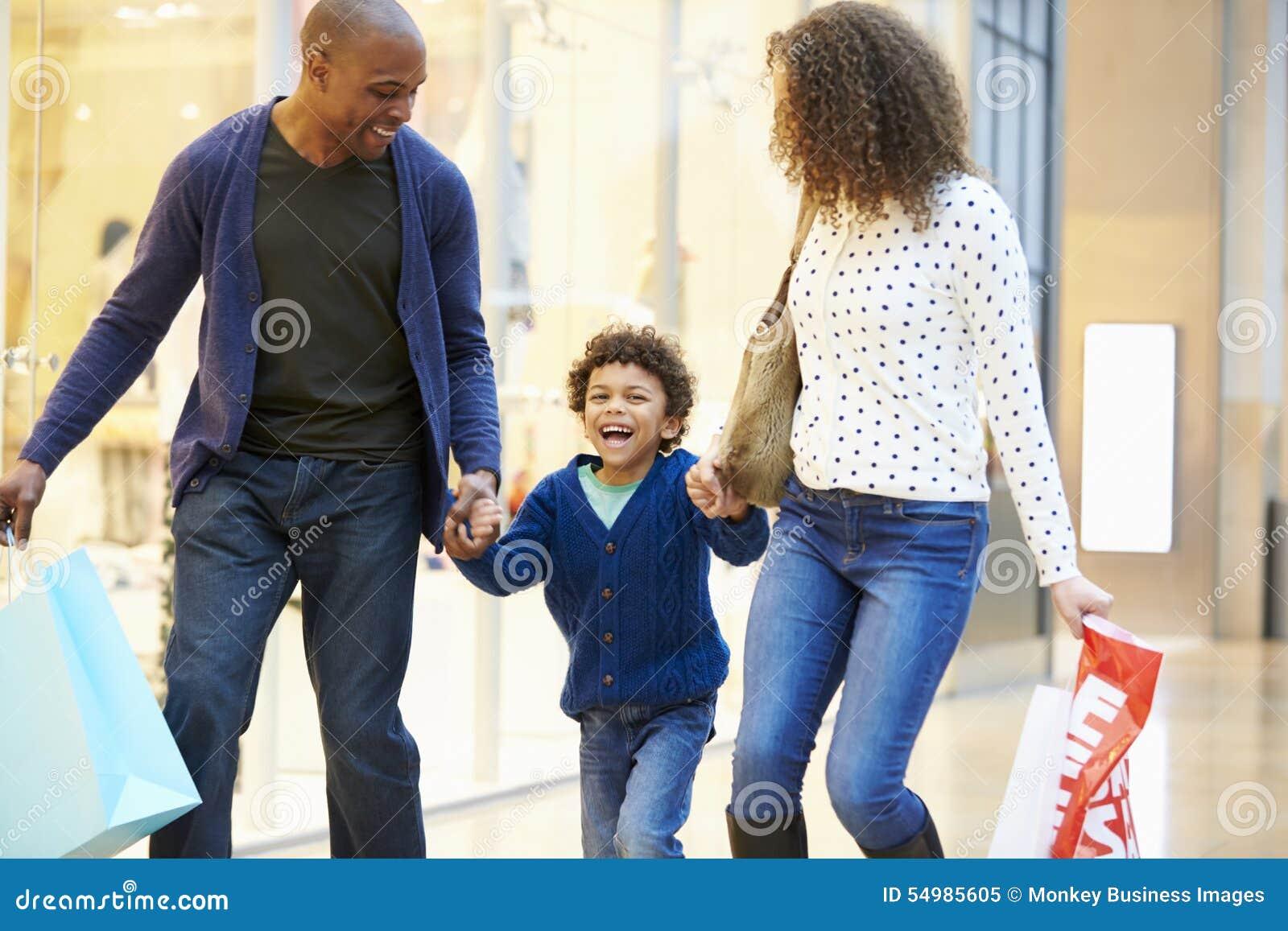 Barn på tur till shoppinggallerian med föräldrar