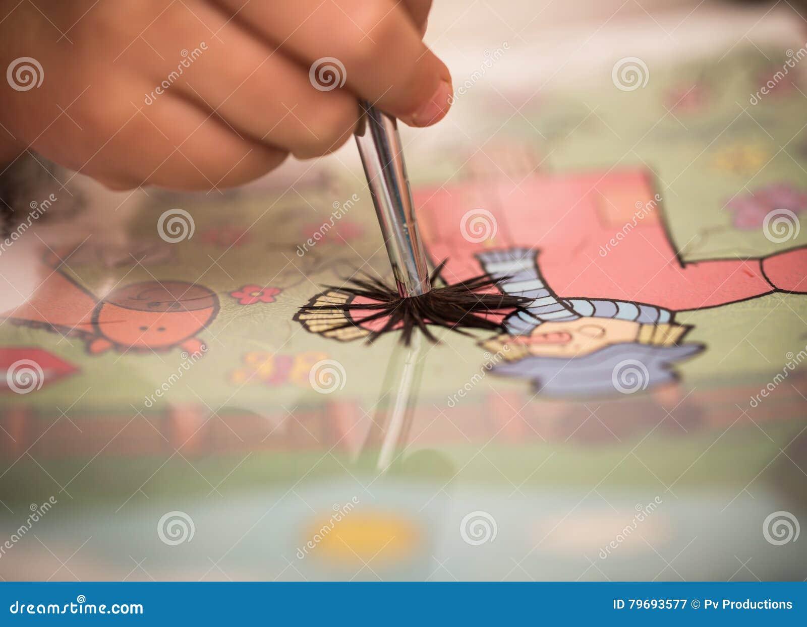 Barn räcker med målarfärger för en borste på vitbok