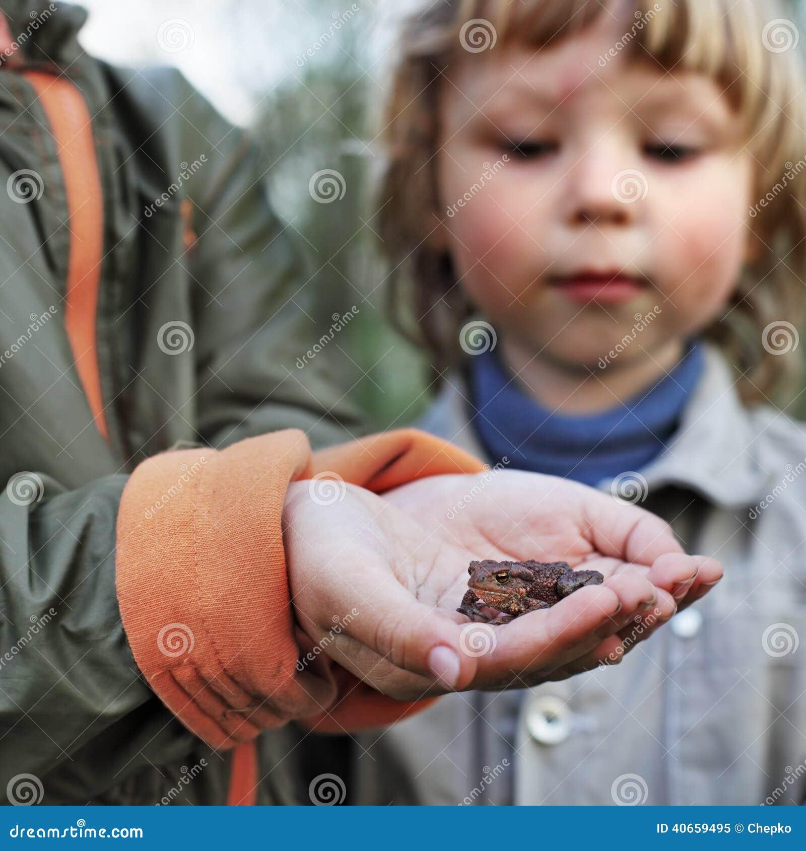 Barn ser en padda grunda i skogen