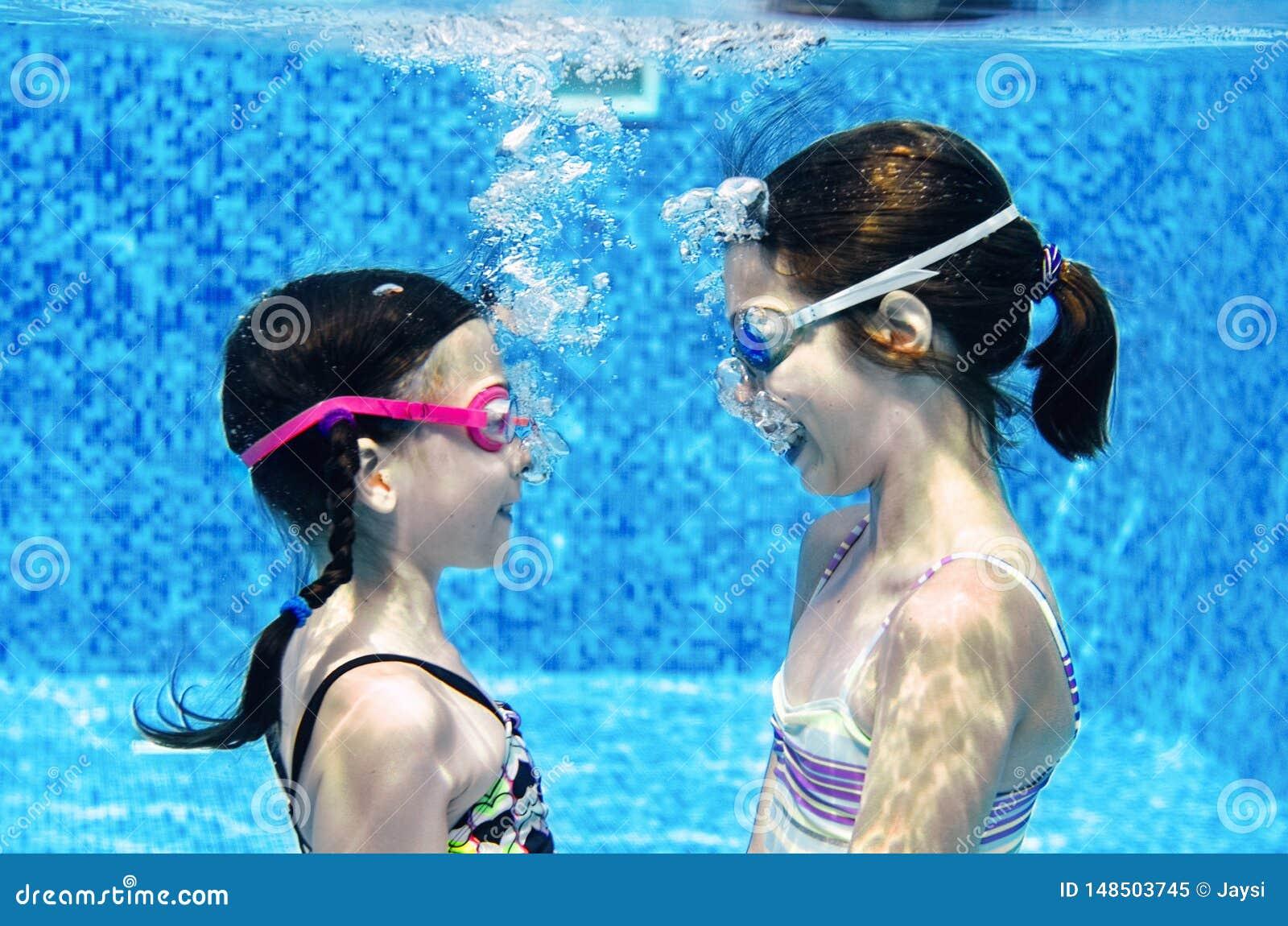 Barn simmar i den undervattens- simbass?ngen, lyckliga aktiva flickor har gyckel under vatten, ungekondition och sport