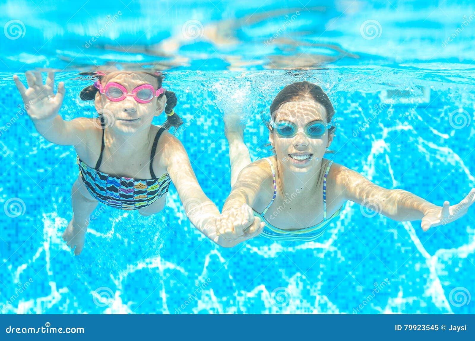 Barn simmar i pöl under vatten, lyckliga aktiva flickor i skyddsglasögon har gyckel, ungesport