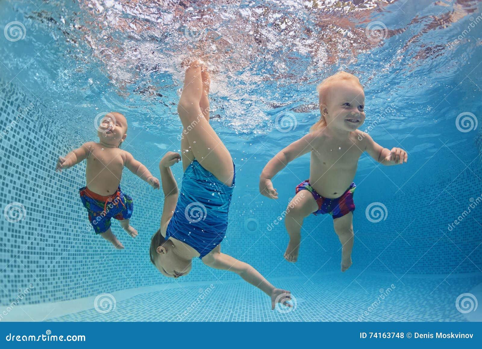 Barn simmar och dyker undervattens- med gyckel i simbassäng