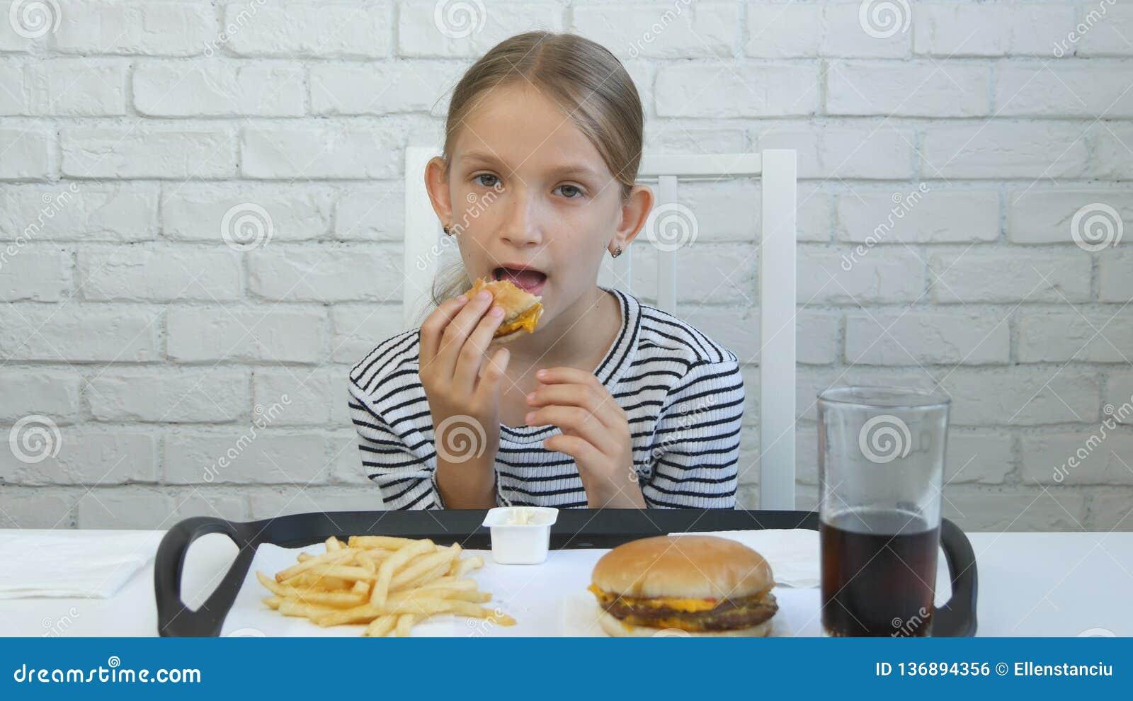 Barn som äter hamburgaren i restaurang, unge och snabbmat, flicka som dricker fruktsaft