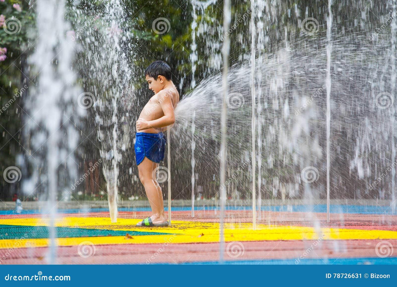 Barn som av offentligt kyler springbrunnen