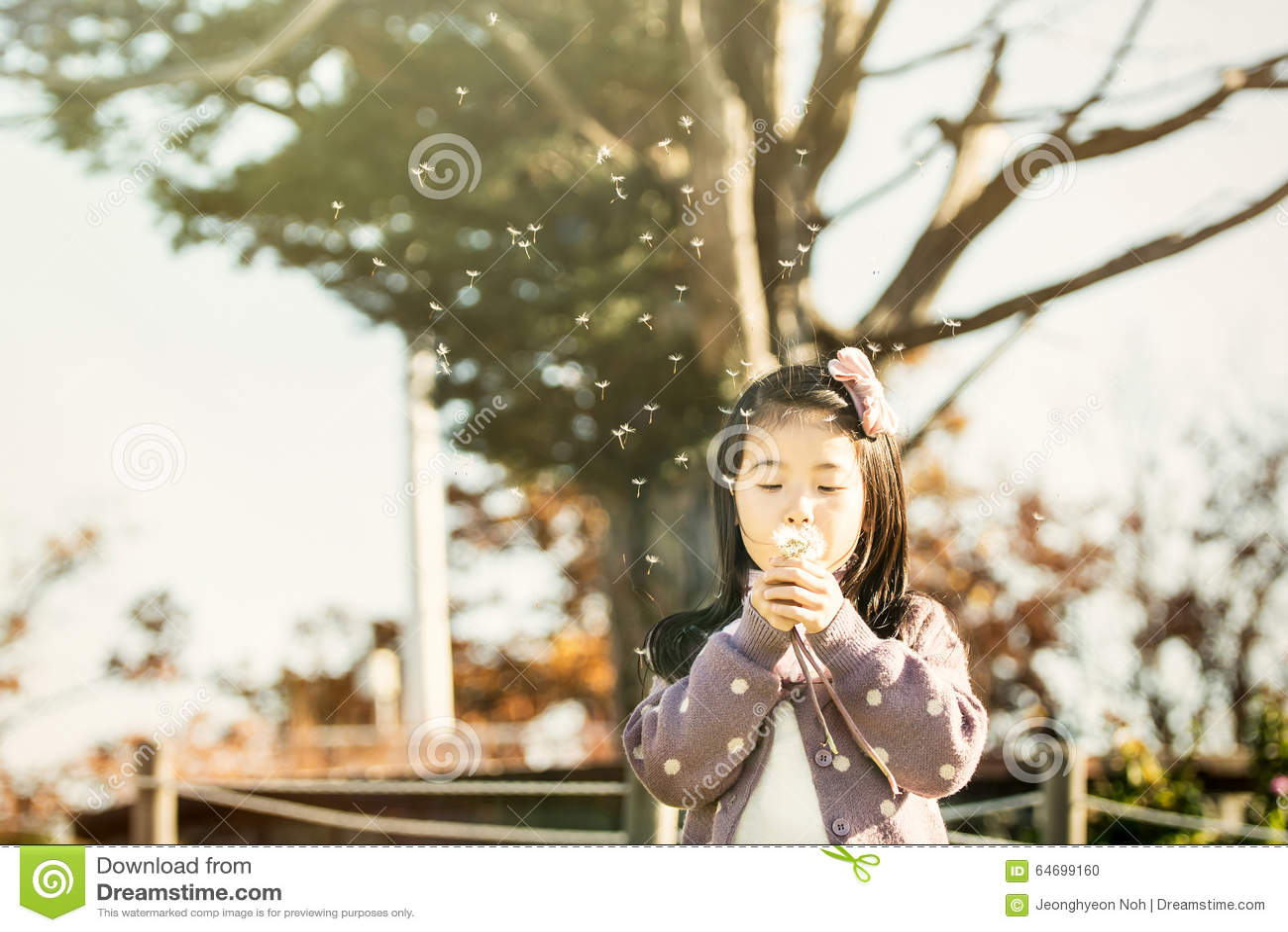 Barn som blåser en maskros i en parkera