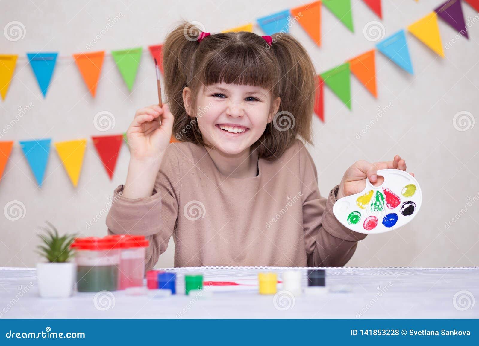 Barn som gör det hemlagade hälsningkortet Lilla flickan målar hjärta på hemlagat hälsa kort som gåvan för mors dag