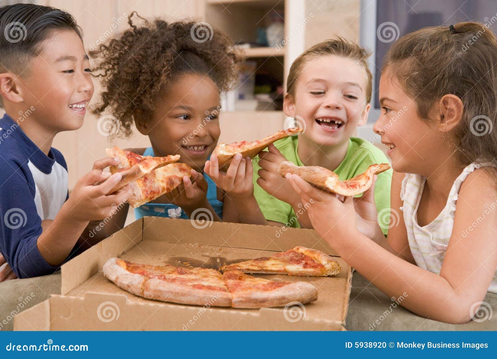 Barn som inomhus äter fyra pizzabarn