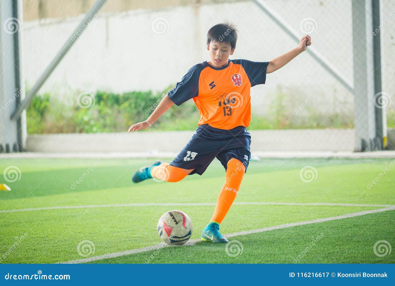 Barn som lär fotboll med föräldrar och lagledare