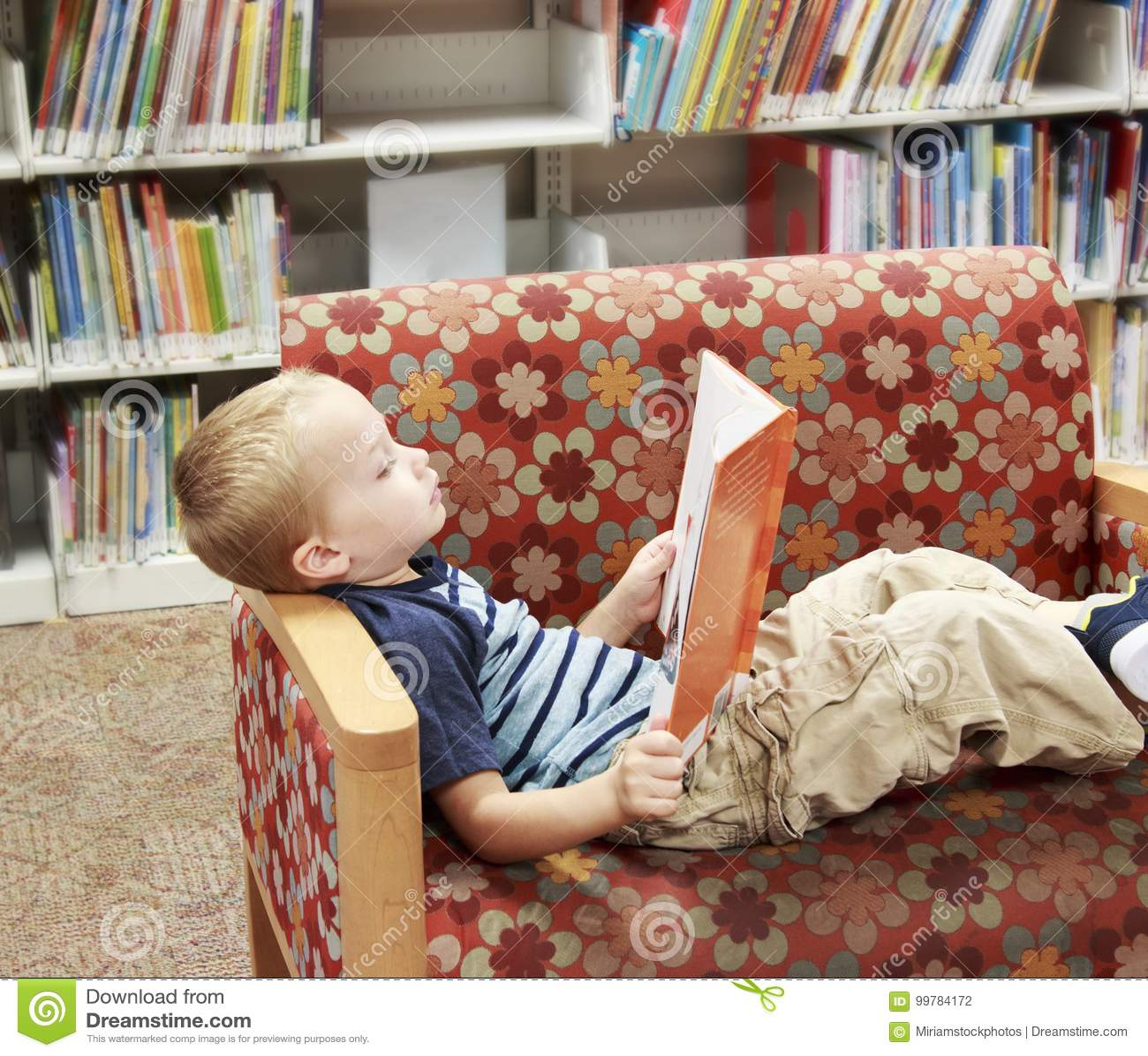 Barn som läser en bok på en soffa på arkivet