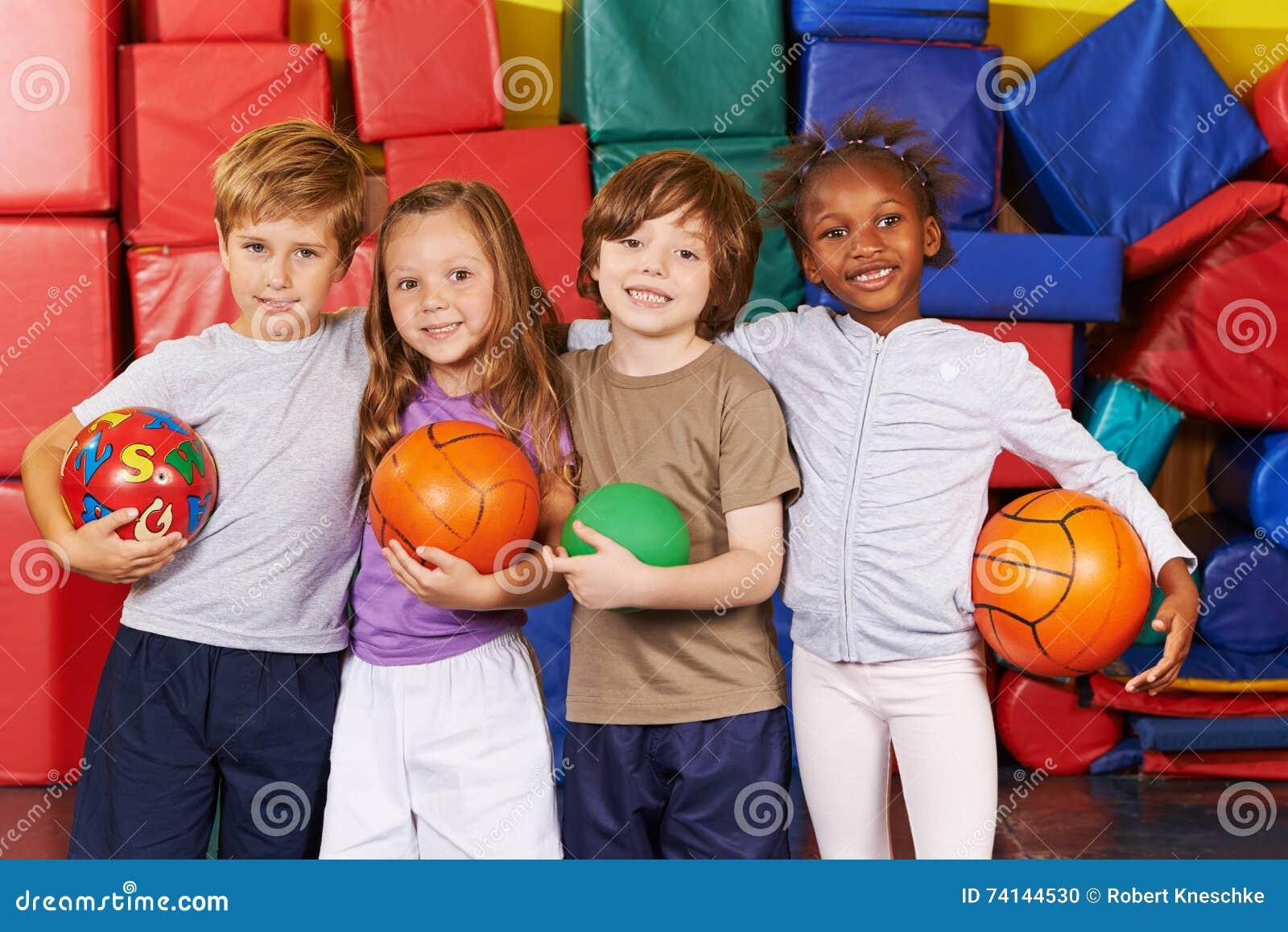 Barn som laget med bollar i idrottshall