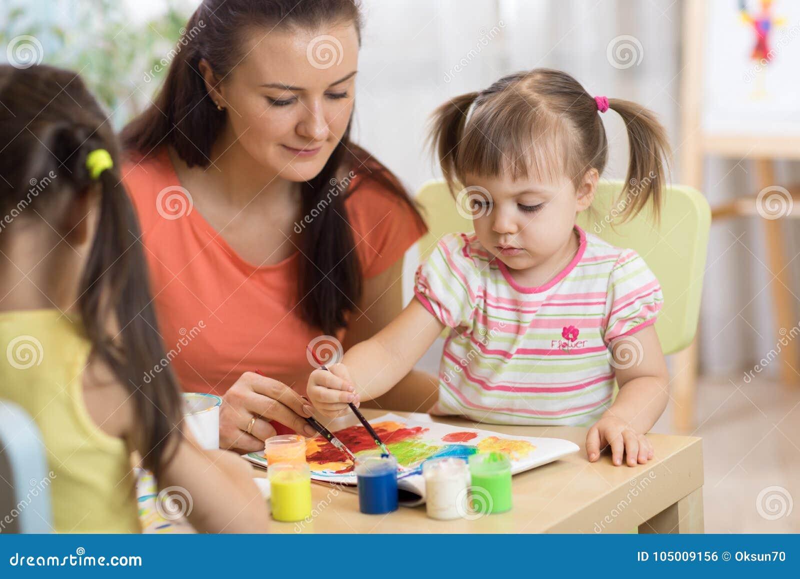 Barn som målar förträningen Lärarehjälp av lilla flickan