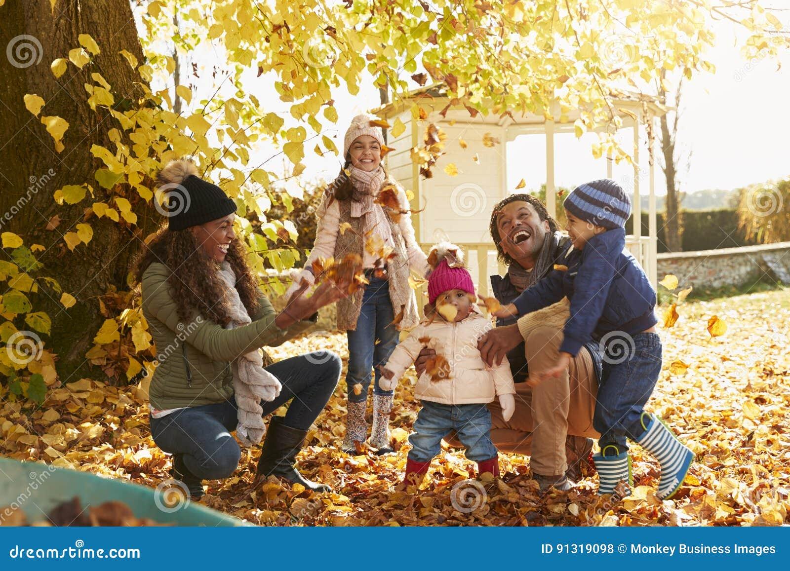 Barn som mot efterkrav hjälper föräldrar till Autumn Leaves In Garden