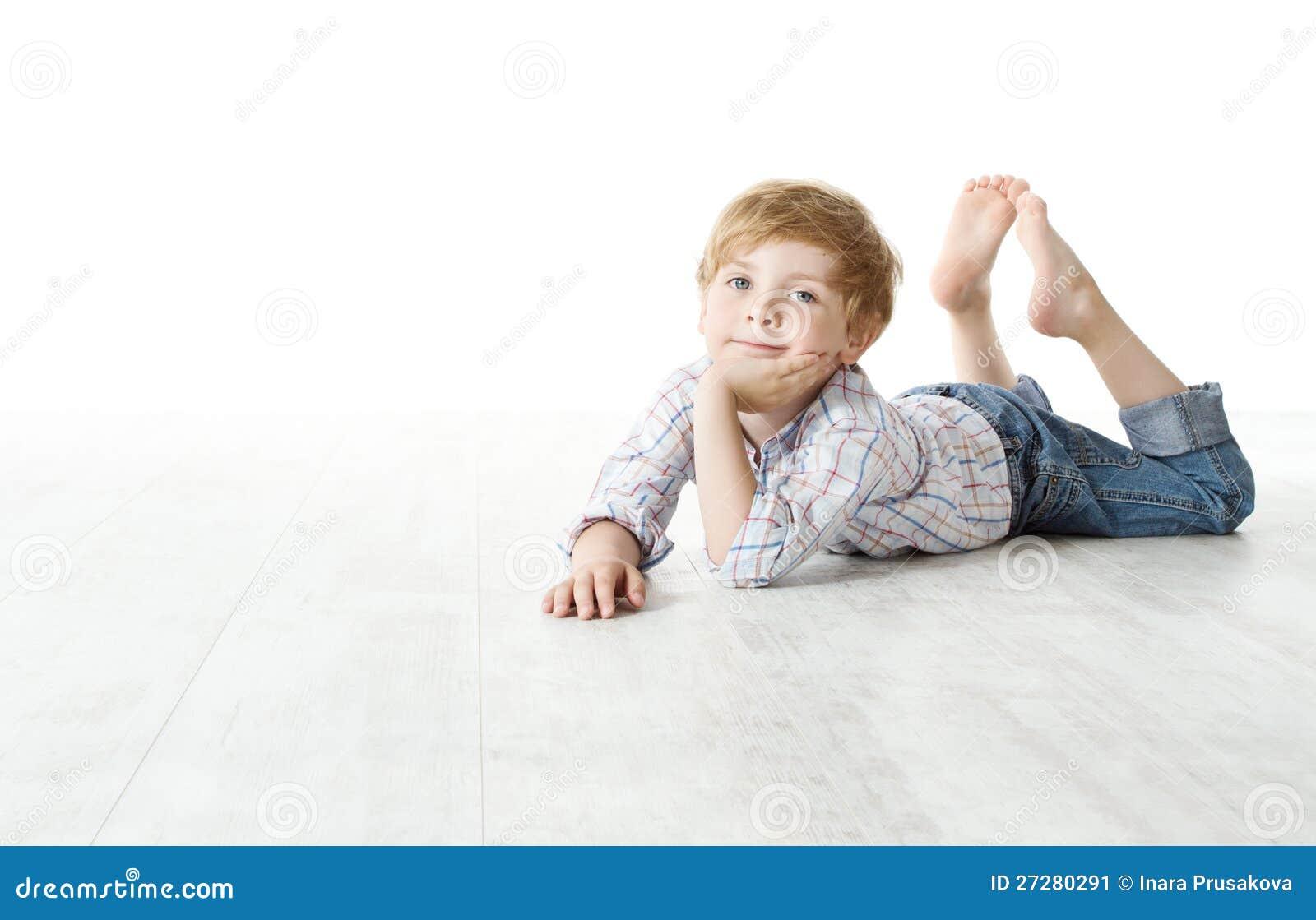 Barn som ner ligger på golv och ser kameran
