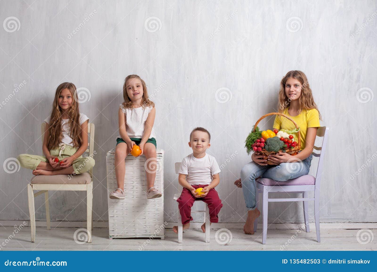 Barn som rymmer en korg av ny frukt och sund mat för grönsaker