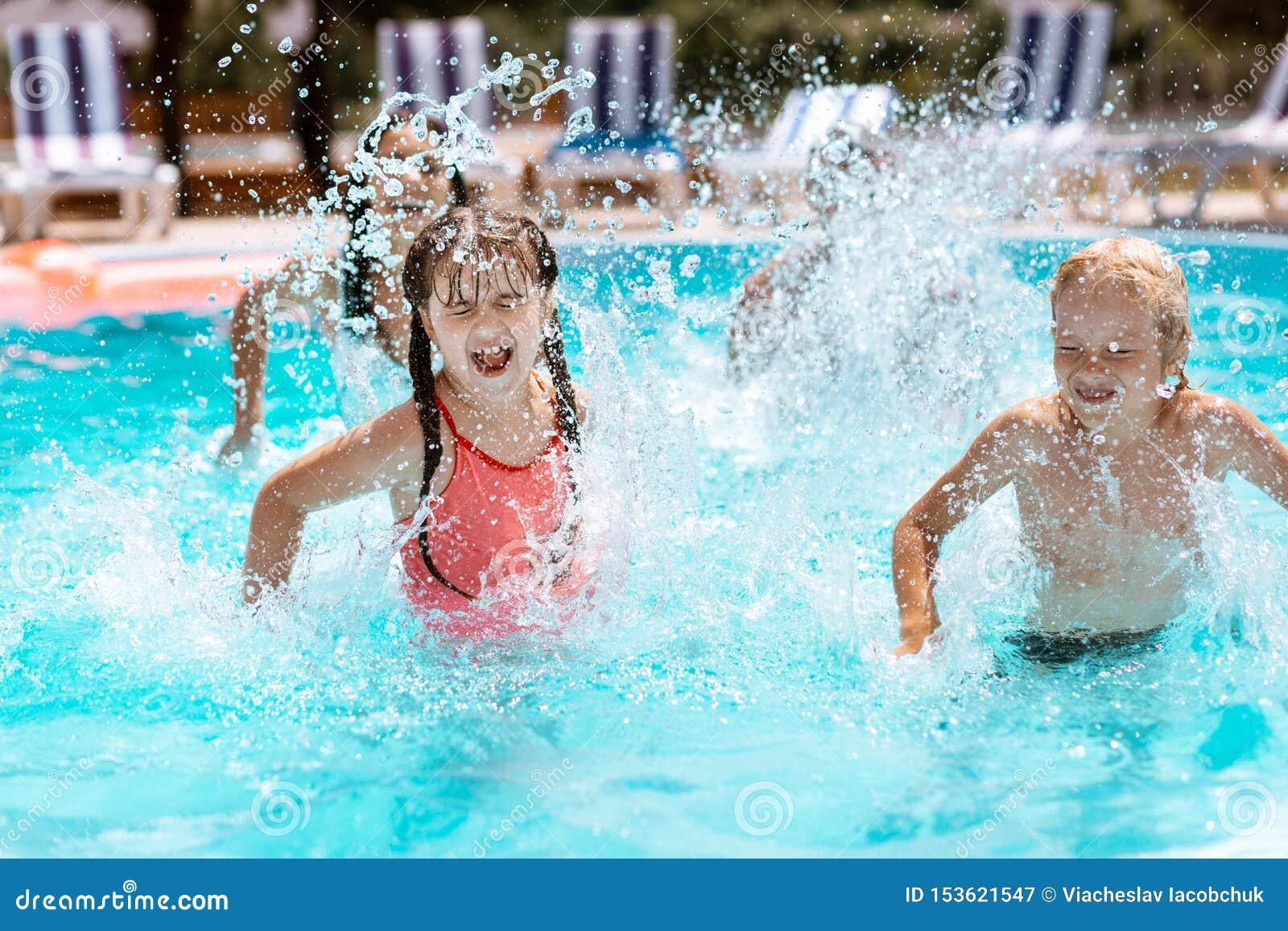 Barn som skrattar, medan plaska vatten i simbassäng