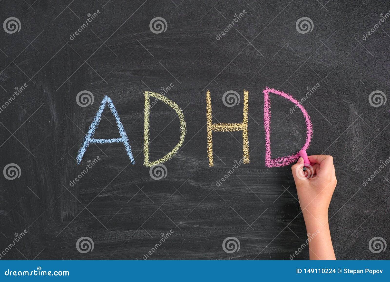 Barn som skriver f?rkortningen ADHD p? en svart tavla