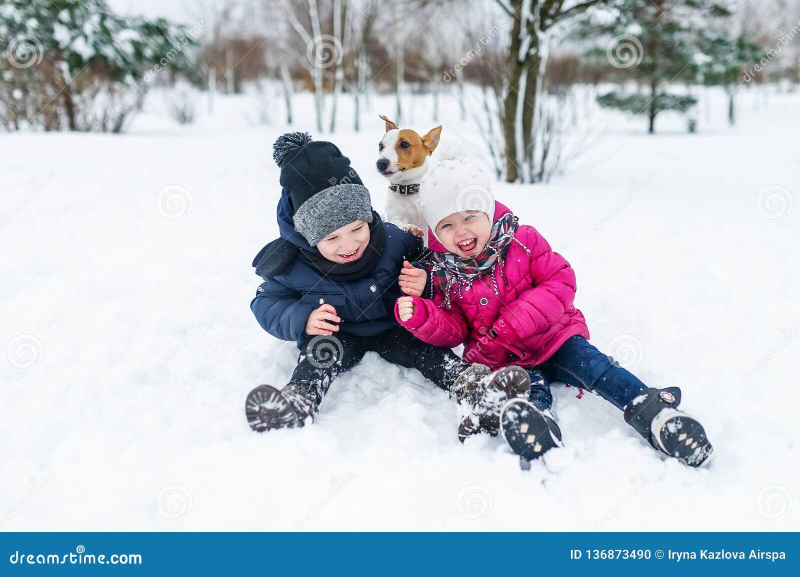 Barn som spelar med den Jack Russell terriervalpen i, parkerar i vintern i snön