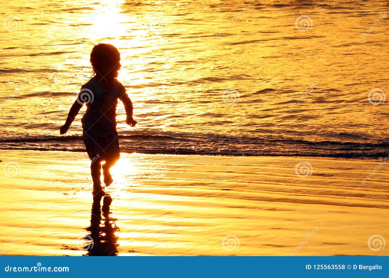 Barn som spelar på stranden i Bali, Indonesien under en guld- solnedgång Havet gillar guld
