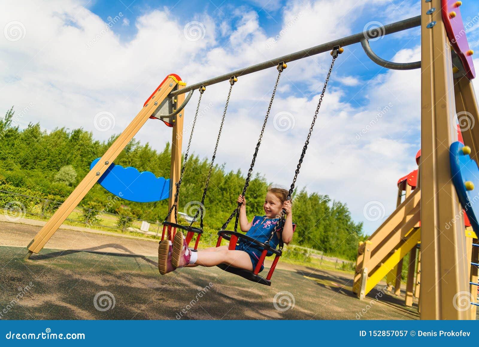 Barn som spelar p? utomhus- lekplats i regn Ungar spelar p? skola- eller dagisg?rd Aktiv unge p? f?rgrik gunga Sunt