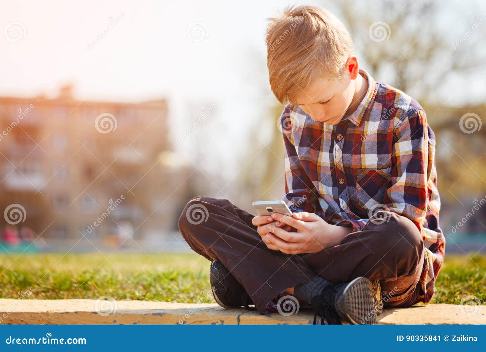 Barn Som Spelar Telefonen Utomhus I Solig Dag Fotografering för ... db998b35198b6
