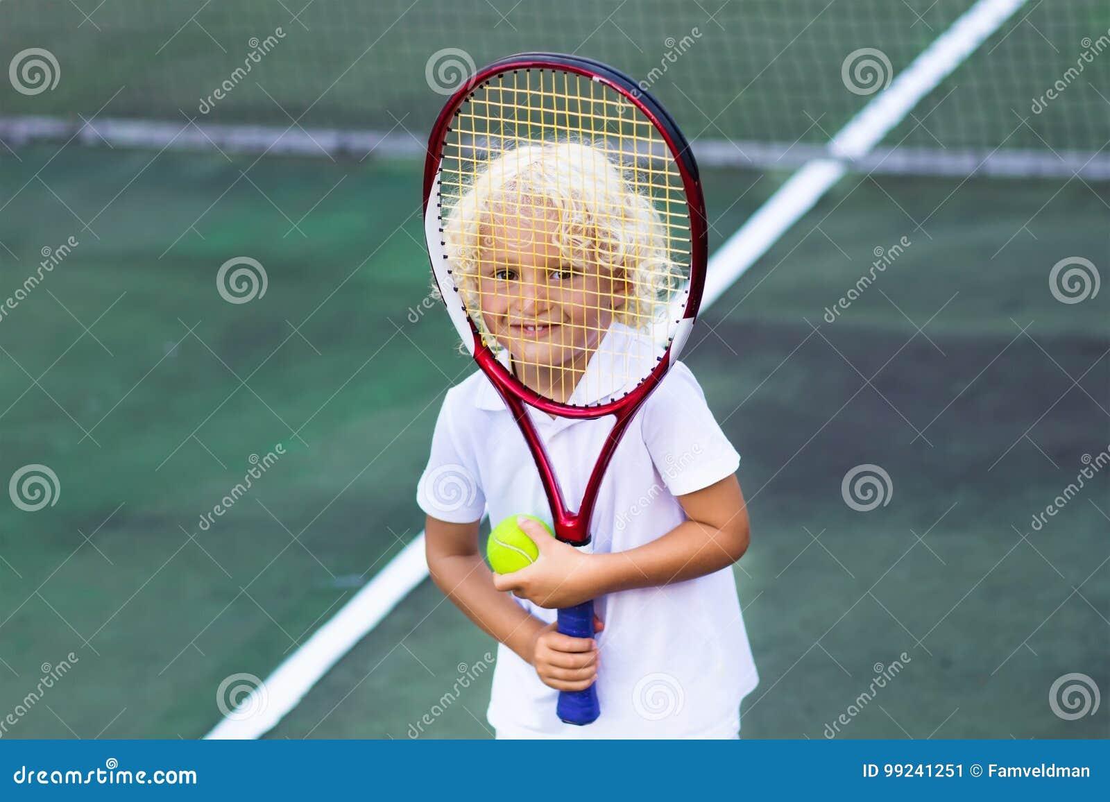Barn Som Spelar Tennis På Den Utomhus- Domstolen Fotografering för ... bd74e3cb73194