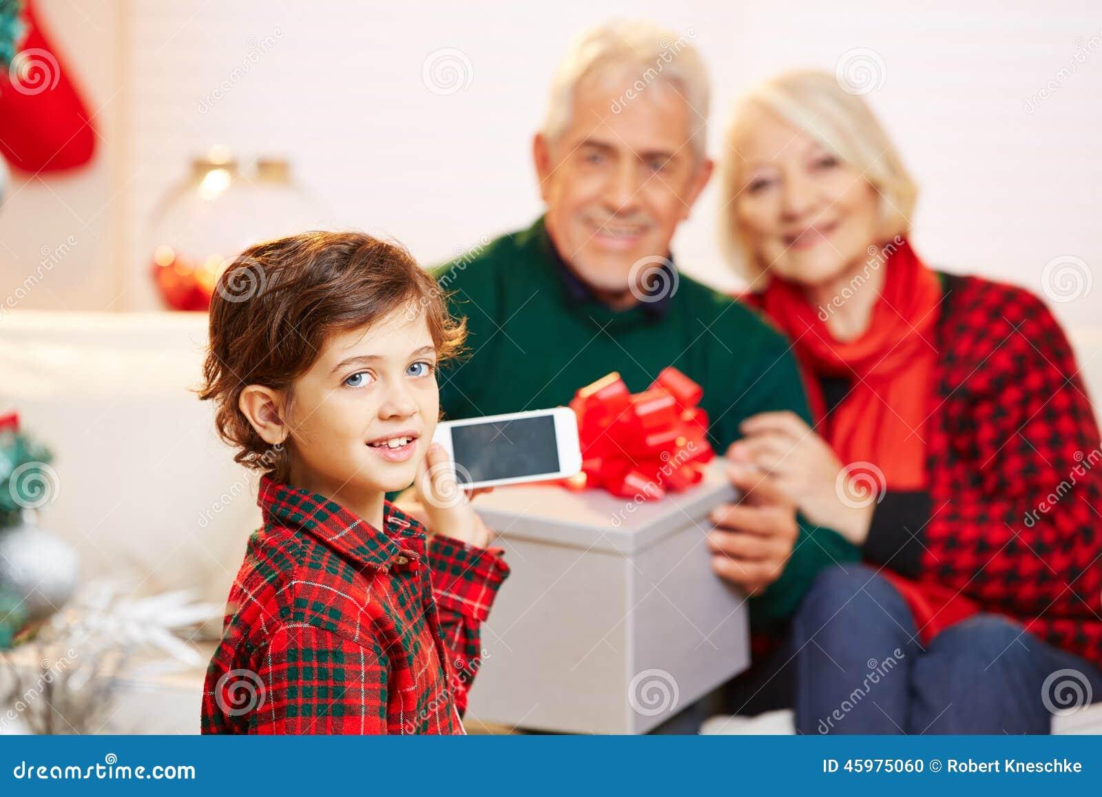 Barn som tar smartphonebilden av morföräldrar