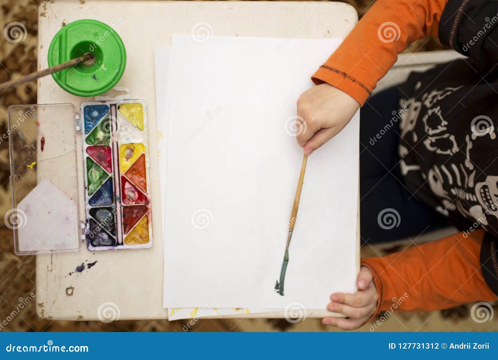 Barn som tecknar övre sikt lego för hand för byggnadsbegreppskreativitet upp väggen