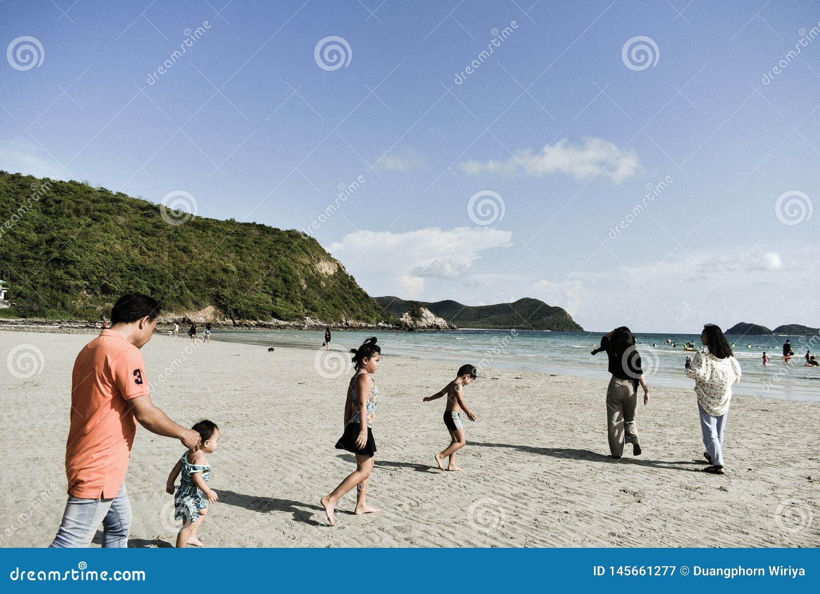 Barn som tillsammans körs till stranden på det Namsai strandSattahip området Thailand