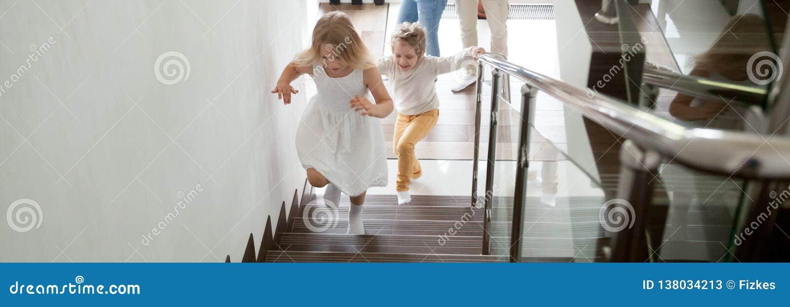 Barn som uppför trappan går till det andra golvet deras nya moderna hus