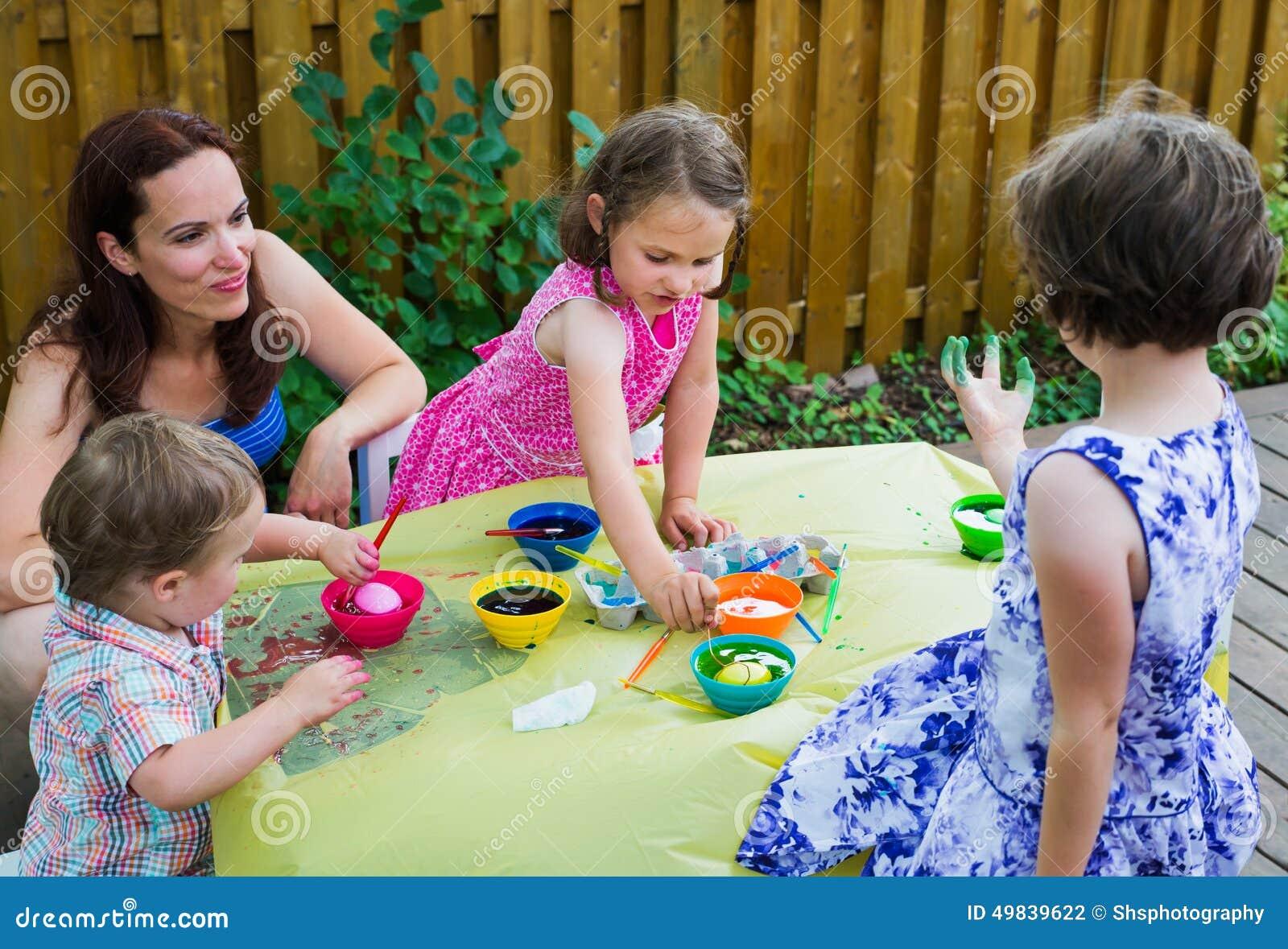 Barn som utanför färgar påskägg