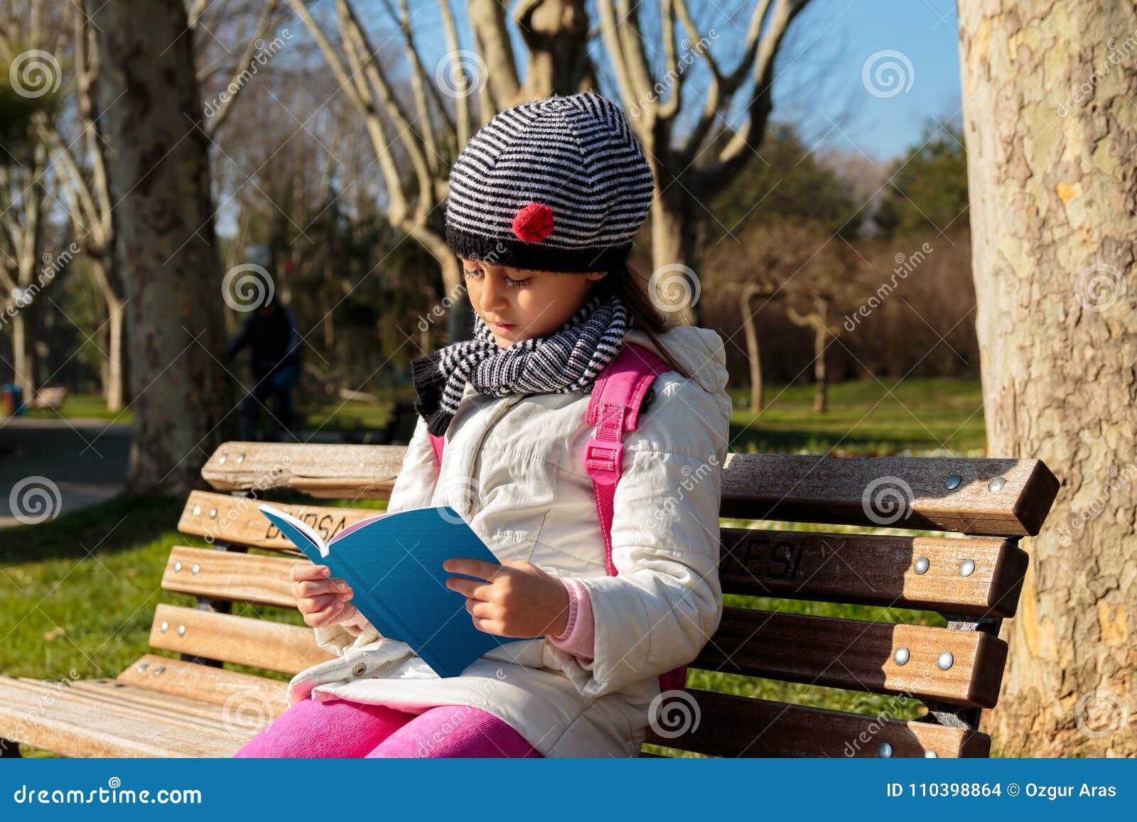 Barn som utomhus läser boken i parkera