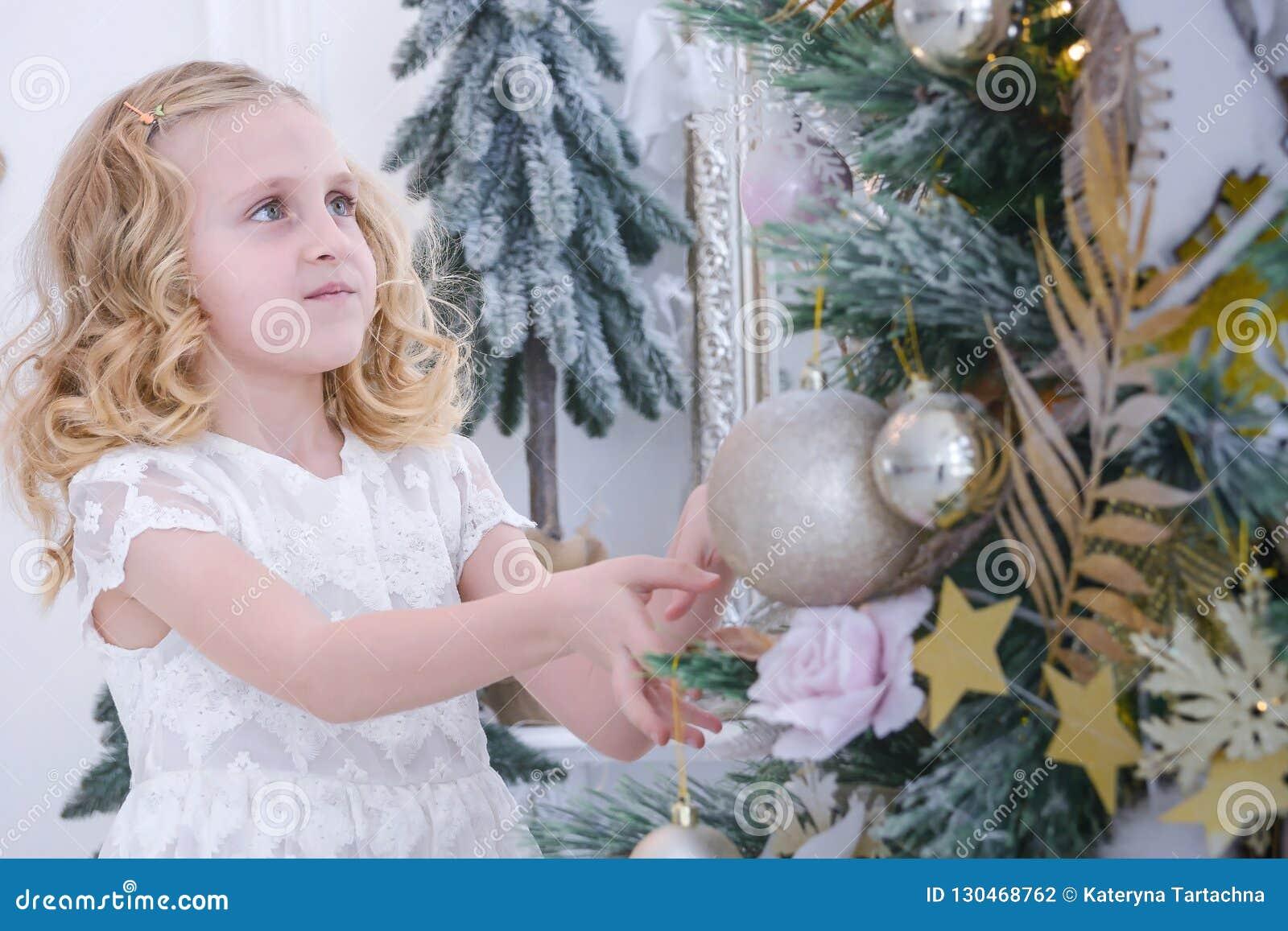 Barn som väntar på det nya året Gullig liten flicka som dekorerar julgranen