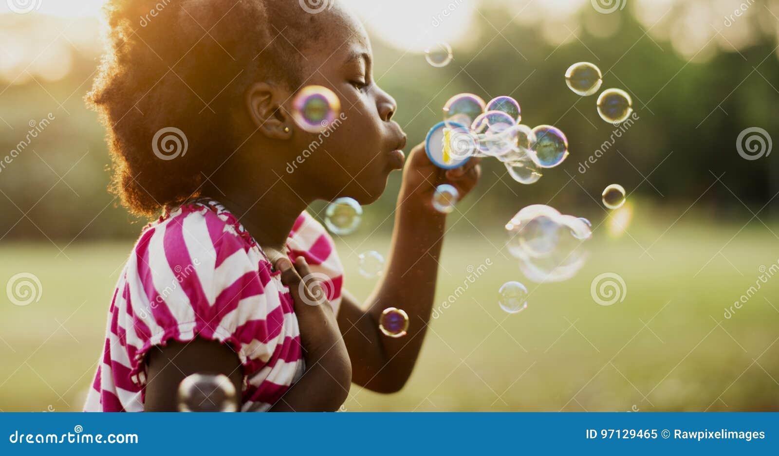 Barn spelar bubblor i en parkera