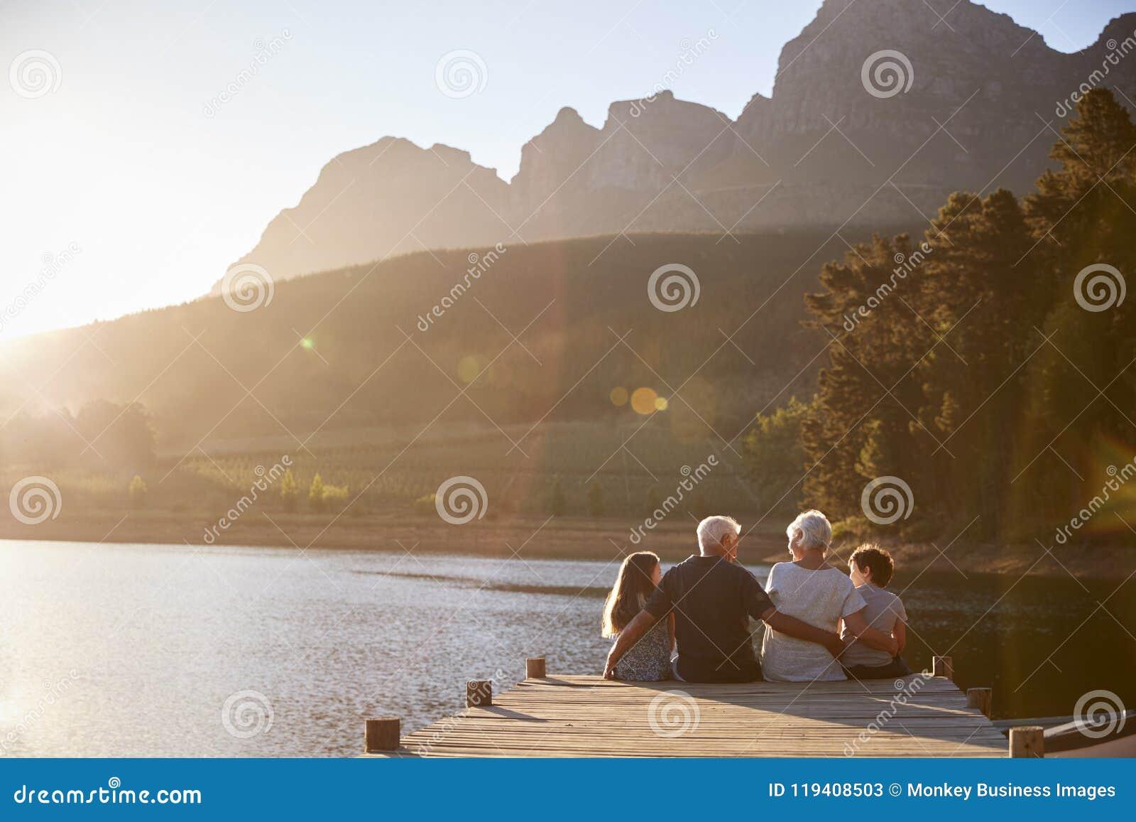 Barnbarn med morföräldrar som sitter på träbryggan vid sjön