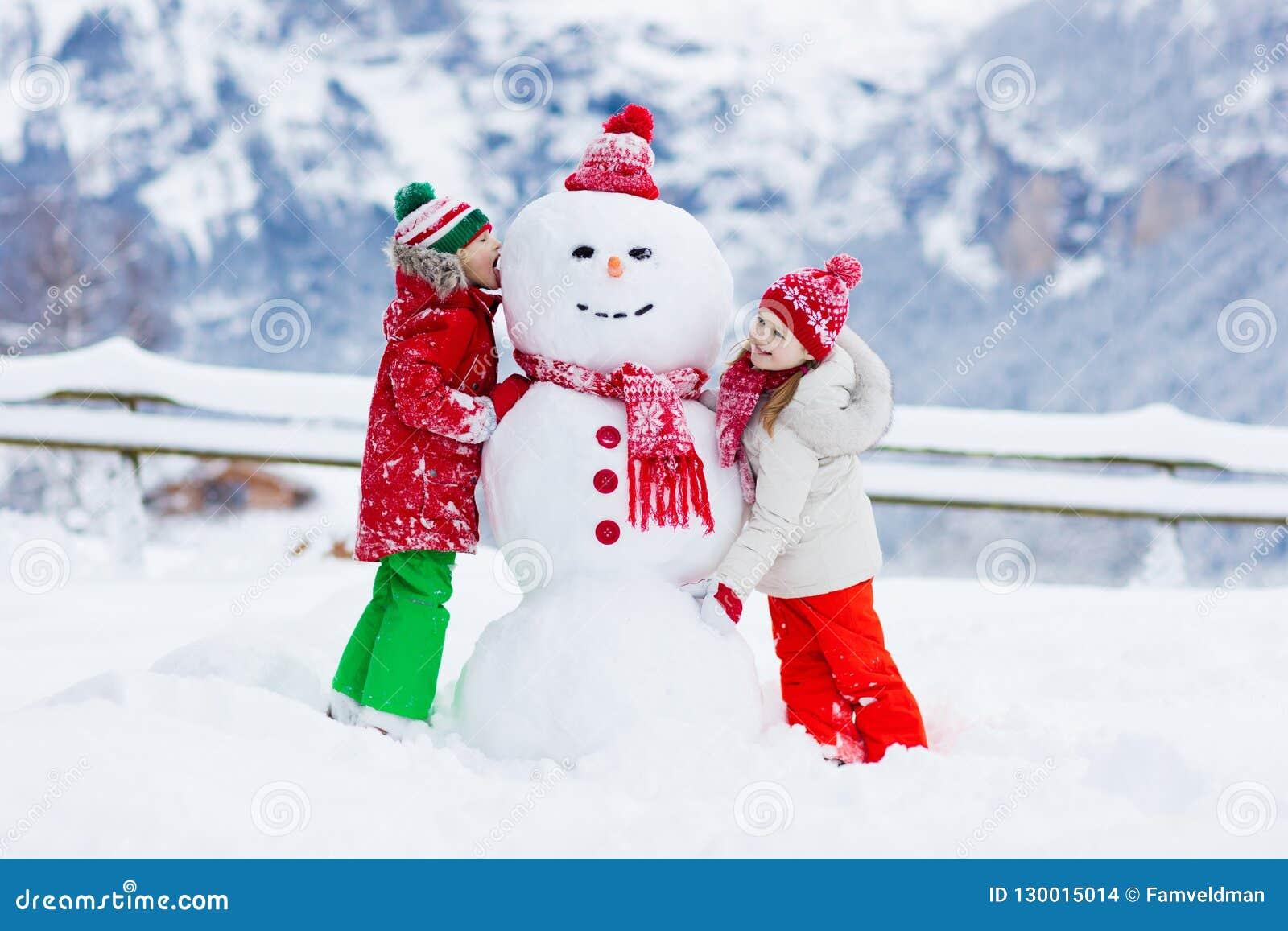 Barnbyggnadssnögubbe Ungar bygger snömannen
